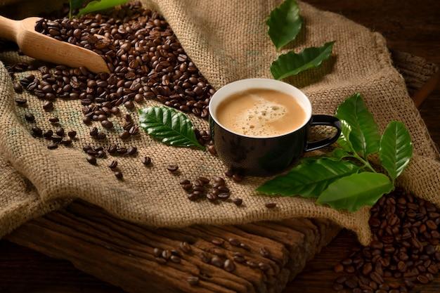 Xícara de café com fumaça e grãos de café em saco de estopa na velha mesa de madeira