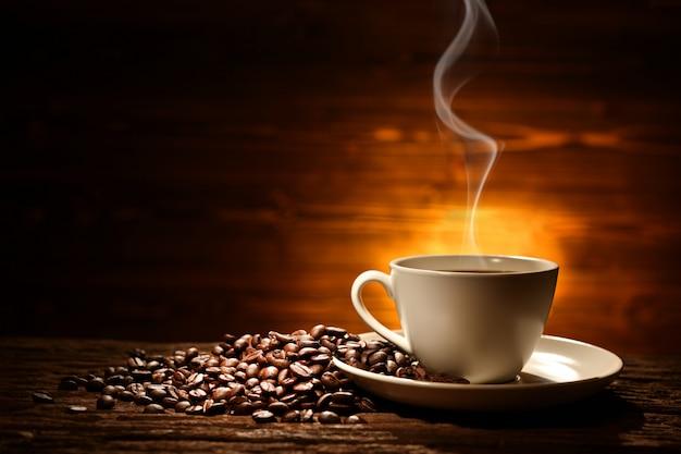 Xícara de café com fumaça e grãos de café sobre fundo de madeira velho