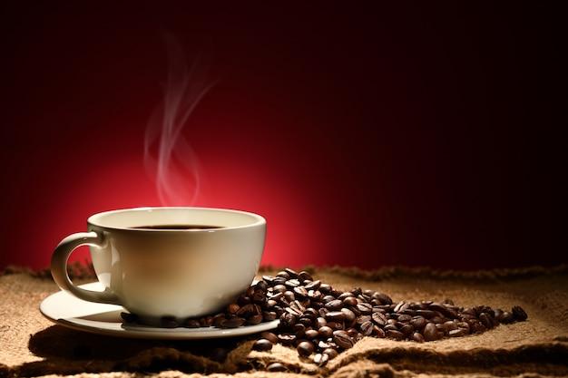 Xícara de café com fumaça e grãos de café sobre fundo marrom avermelhado