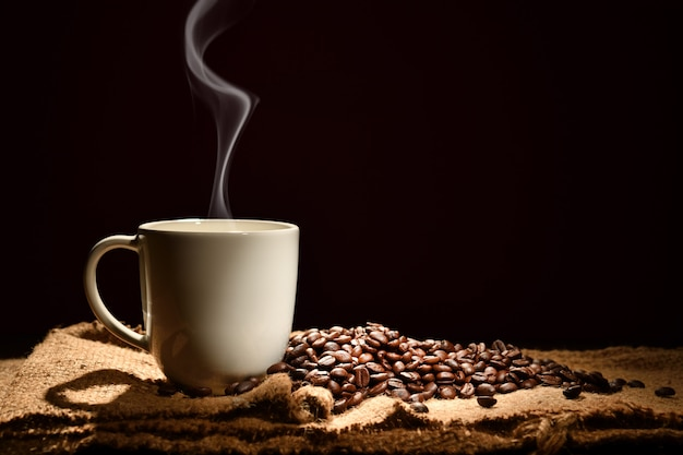 Xícara de café com fumaça e grãos de café sobre fundo preto