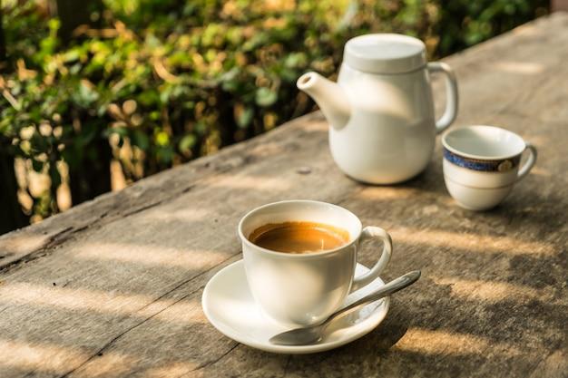 Xícara de café com fundo de bules na mesa de madeira com luz solar