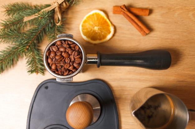 Xícara de café com galhos secos de laranja e abeto e passo fazendo café com feijão em cima da mesa.