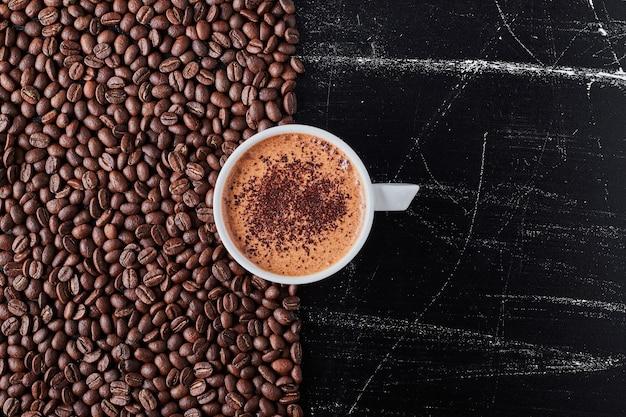 Xícara de café com grãos ao redor.