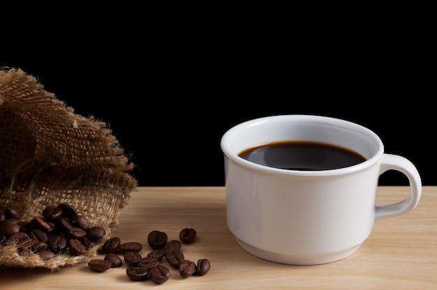 Xícara de café com grãos de café, derramando fora do saco de serapilheira na mesa de madeira