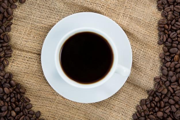 Xícara de café com grãos de café dispostos em saco