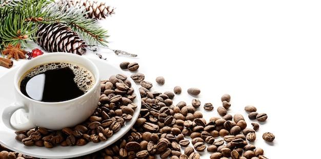 Xícara de café com grãos de café e enfeites de natal em fundo branco