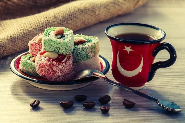 Xícara de café com grãos de café e manjar turco deitado no pires com colher de prata na placa de madeira