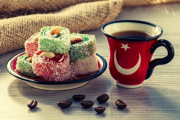 Xícara de café com grãos de café e manjar turco deitado no pires na placa de madeira
