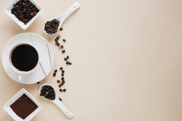 Xícara de café com grãos de café e pó de café sobre fundo bege