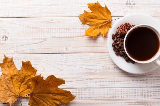 Xícara de café com grãos de café espalhados, folhas amarelas secas em uma mesa de madeira. humor de manhã de outono, copyspace.