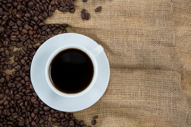 Xícara de café com grãos de café no saco