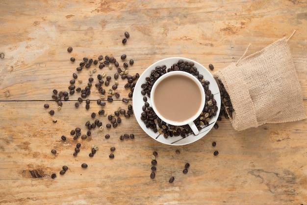 Xícara de café com grãos de café torrados e crus, caindo do saco sobre o pano de fundo de madeira