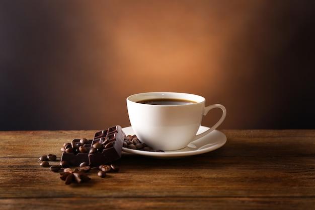 Xícara de café com grãos e chocolate na mesa de madeira em fundo escuro