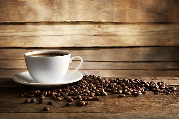 Xícara de café com grãos na mesa de madeira