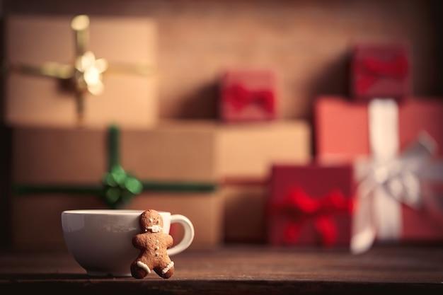 Xícara de café com homem-biscoito e presente de natal na mesa de madeira