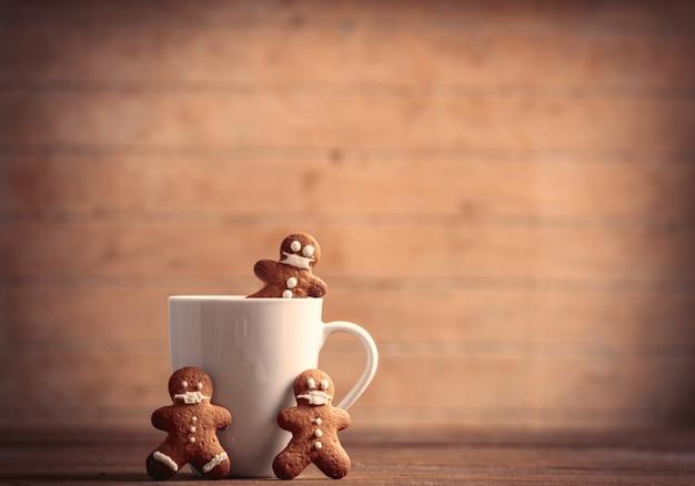Xícara de café com homem-biscoito na mesa de madeira