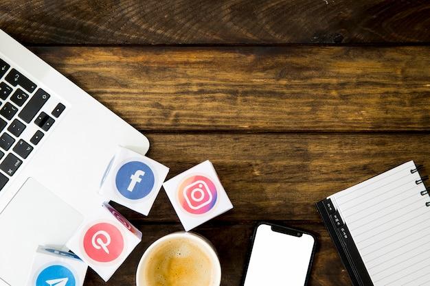 Xícara de café com ícones de aplicativos perto de celular e laptop