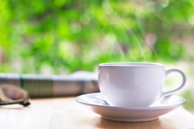 Xícara de café com jornal e óculos sobre a mesa de madeira, fundo verde bokeh