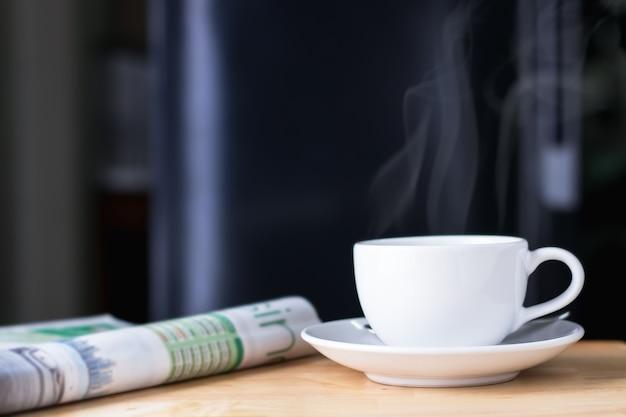 Xícara de café com jornal sobre a mesa de madeira, fundo preto