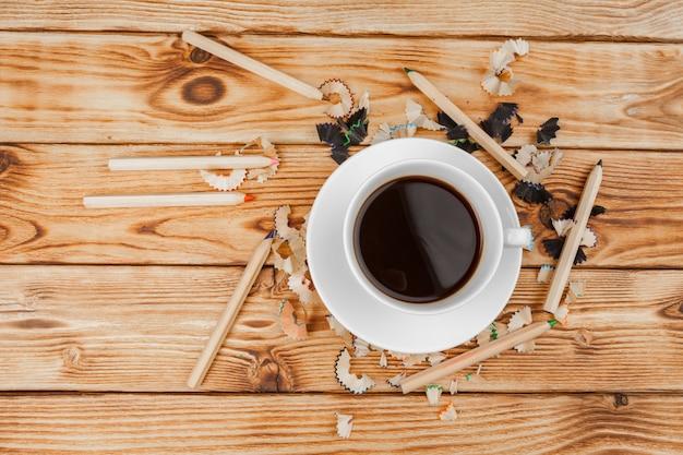 Xícara de café com lápis e lápis corta em fundo de madeira