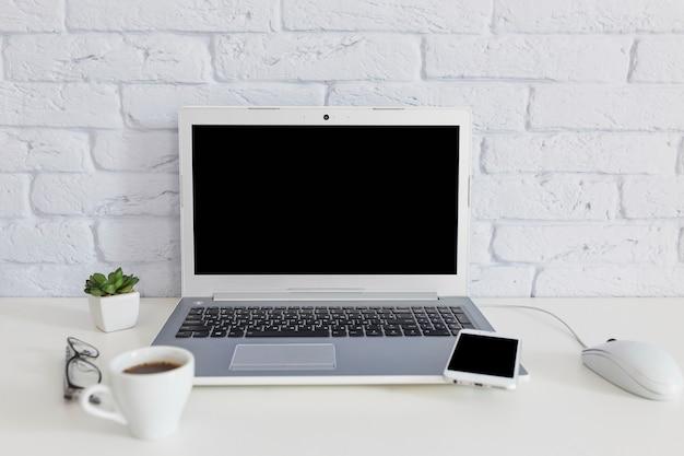 Xícara de café com laptop e celular na mesa branca