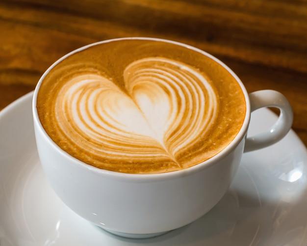Xícara de café com latte art em madeira