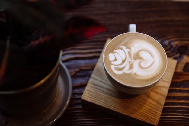 Xícara de café com latte art na mesa de madeira.