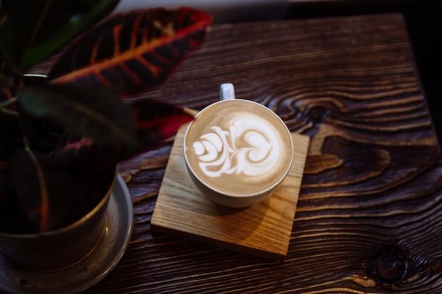 Xícara de café com latte art próximo à planta de interior