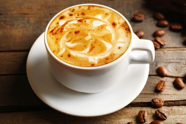 Xícara de café com leite arte com grãos na mesa de madeira, closeup