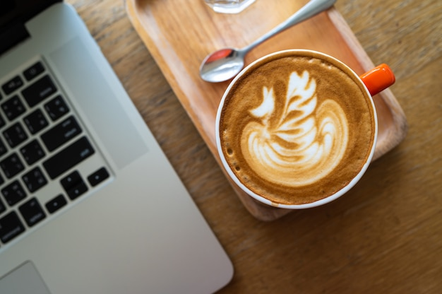 Xícara de café com leite arte na mesa de madeira com computador lapop