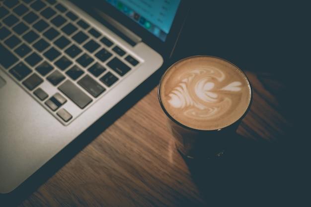 Xícara de café com leite bem feito ao lado de um laptop