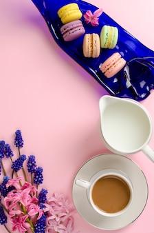 Xícara de café com leite, biscoitos e leite jarra em rosa pastel