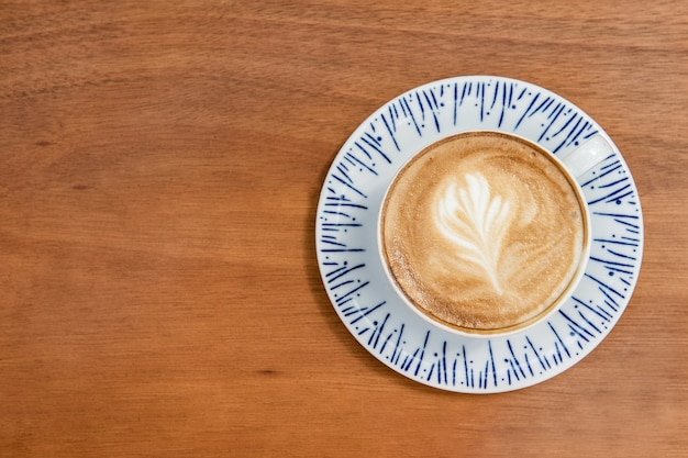 Xícara de café com leite com arte de design de folhas em espuma, em uma mesa de madeira e vista de cima