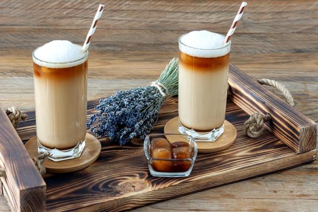Xícara de café com leite com calda caseira de lavanda e flores em uma bandeja de madeira. café da manhã aconchegante.