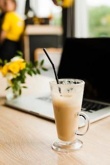 Xícara de café com leite com canudo na frente da desfocagem laptop na mesa