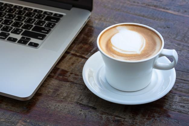 Xícara de café com leite com computador portátil na mesa de madeira