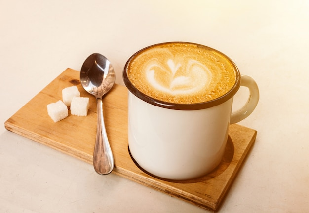 Xícara de café com leite com espuma, colher e açúcar