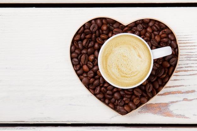 Xícara de café com leite com espuma sobre o coração do grão de café. conceito de amor do café. madeira branca na superfície.
