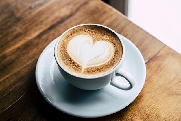 Xícara de café com leite com formato de coração em fundo de madeira velho ao sol da manhã