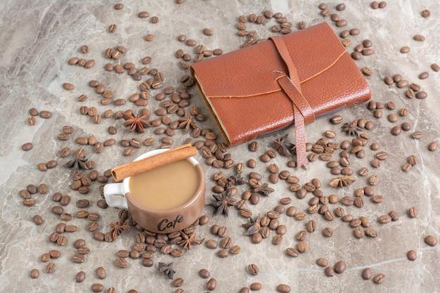 Xícara de café com leite com grãos de café e caderno.