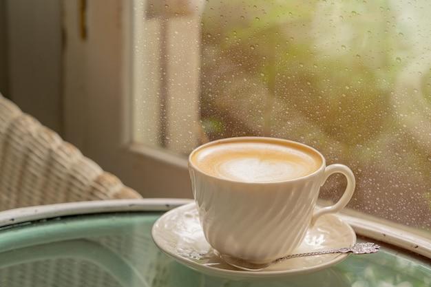 Xícara de café com leite com latte art perto das janelas com queda de chuva após a chuva da manhã