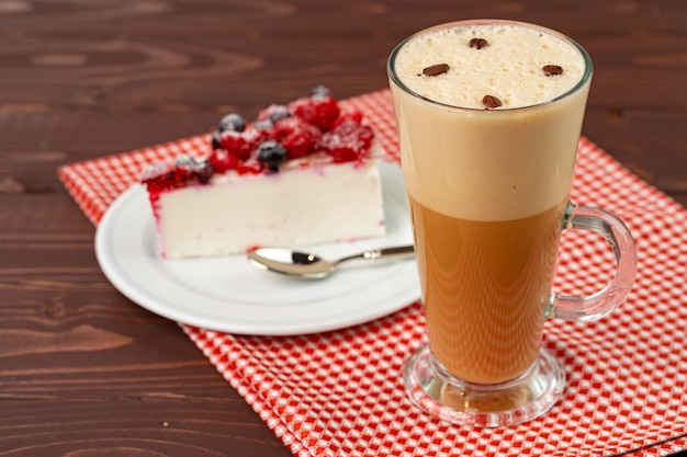 Xícara de café com leite com pedaço de cheesecake de frutas vermelhas