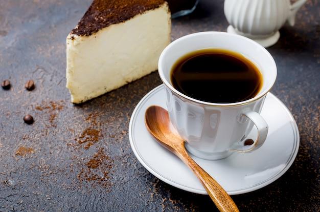 Xícara de café com leite com um pedaço de queijo no café moído
