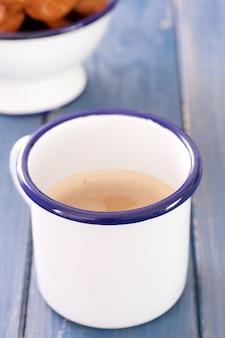 Xícara de café com leite e biscoitos em madeira azul
