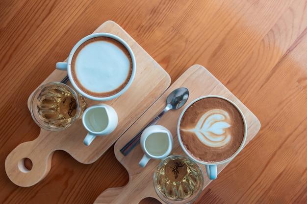 Xícara de café com leite e cappuccino em uma placa de madeira com a arte do café com leite na cafeteria, xícara de café com chá e xarope.
