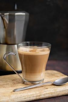 Xícara de café com leite e colher de chá na mesa de madeira e a cafeteira italiana no fundo. vertical