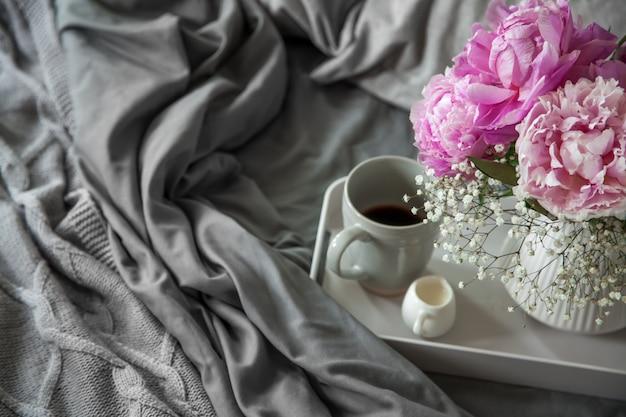Xícara de café com leite e flores em uma bandeja na cama
