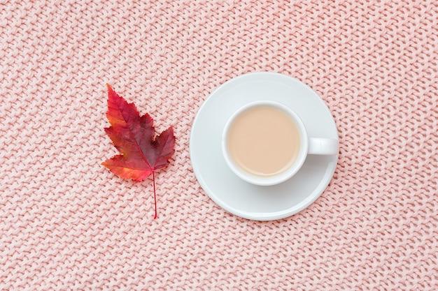 Xícara de café com leite e folha de outono vermelha em rosa pastel de fundo xadrez de malha. outono aconchegante.