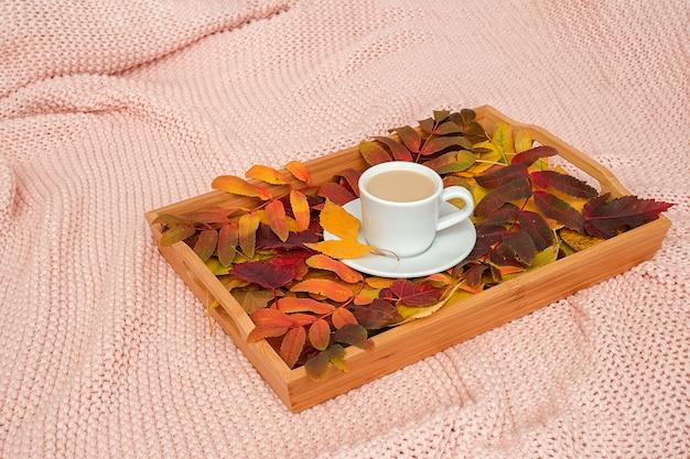 Xícara de café com leite e folhas coloridas variadas na bandeja de madeira em xadrez rosa. conceito outono acolhedor