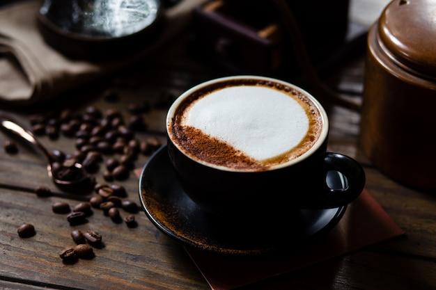 Xícara de café com leite e grãos de café com gotejador de café em conjunto na mesa de madeira.